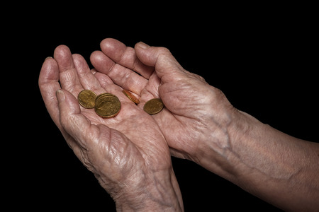Senior woman hands holding some euro coins. Pension, poverty, social problems and senility theme. Isolated on black, clipping path included Stock Photo