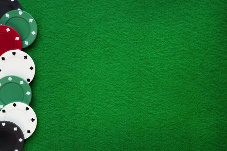 Poker chips on green felt casino table. Gambling, poker, blackjack and roulette theme background