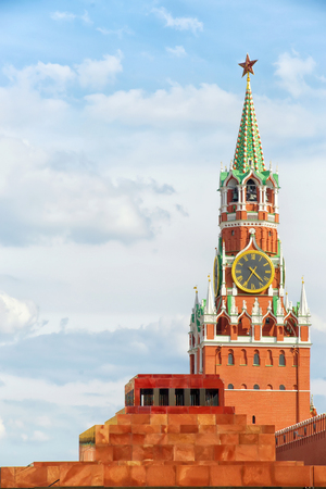 spasskaya: Red square, Moscow, Russia. Spasskaya tower of Kremlin with star and clock and Lenins Mausoleum. Vertical composition, copy space on the cloudy sky. Bright and sunny day  view Stock Photo