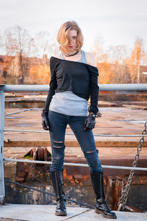 Young stylish aggressive looking woman. Lace-up boots, black leather gloves, ripped jeans, blond hair. Looking at camera. Outdoor portrait