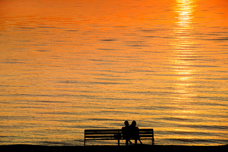 Silhouette of a couple on a bench at sunset against romantic orange colored sea. Summer leisure, vacation and romance theme Stock Photo