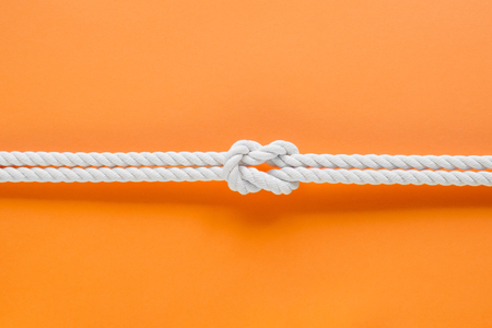 White ship ropes connected by reef knot. On orange background Stock Photo - 80829072