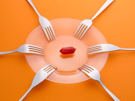One sausage and six forks. Sharing, limited resour?es, shortage and contention concept. On orange background