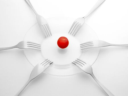 Red tomato and six black and white forks. Sharing, competition, shortage and contention concept. On white background