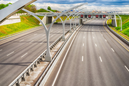 Bright wide high speed highway against distant industrial landscape and dramatic sky. HDR style image Stock Photo
