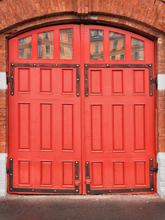 Red wooden gates of vintage fire station. On red brick wall