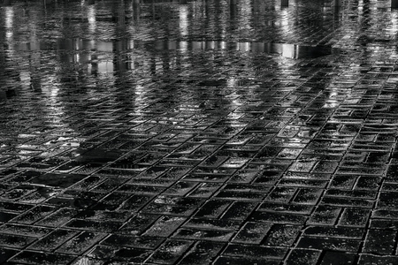 Wet pavement at night. Black and white photo