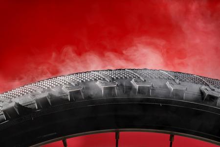 Smoking bike tire. On red background