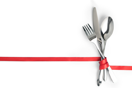 Fork, spoon and knife tied with a red ribbon. Isolated on white