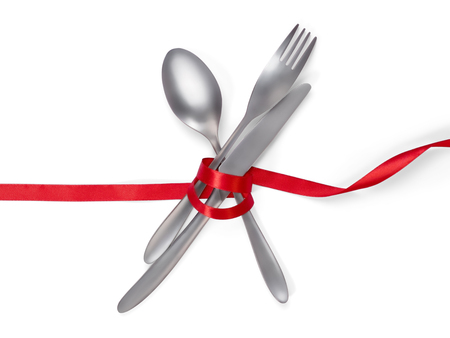 Fork, spoon and knife tied with a red ribbon isolated on white