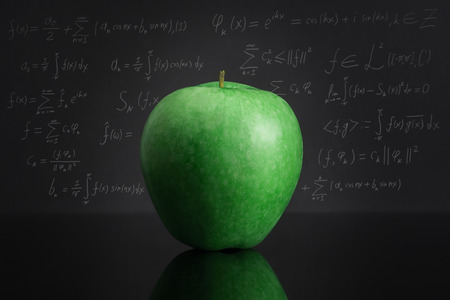 Green apple on black table against blackboard full of complicated mathematical formulas. Knowledge and education theme. (Text its some math magic about Fourier transform) Stock Photo