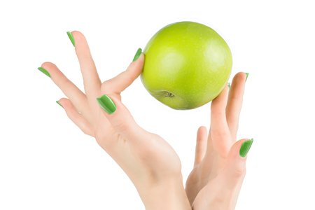 Woman hands with green nails carefully holding green fresh apple. Isolated on white, clipping path included