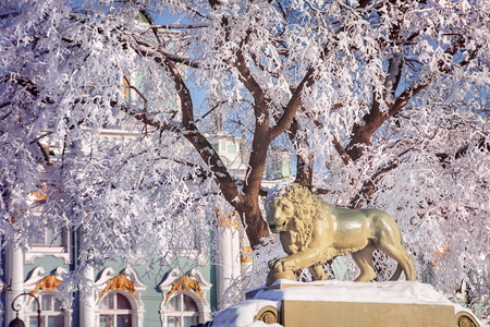 Winter landscape in Saint-Petersburg, Russia. Lion sculpture against snow and Hermitage museum