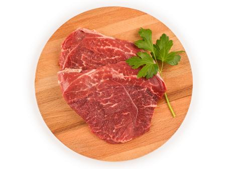 Rohes Fleisch für Steak auf rundem Holzbrett. Draufsicht isoliert auf weiß, Beschneidungspfad enthalten Standard-Bild