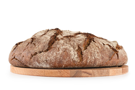 Round freshly baked rustic rye bread on the wooden cutting board. Side view isolated on white, clipping path included