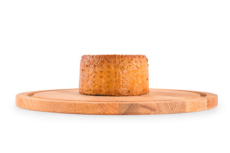 Round smoked cheese on the cutting board. Side view isolated on white, clipping path included
