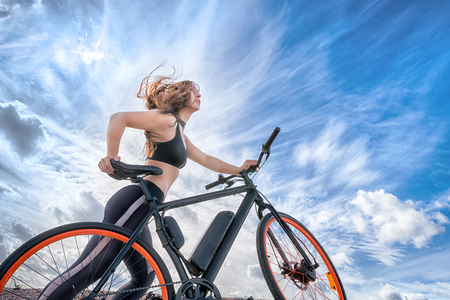 Athletic girl with hair flying in the wind leading electric bike. Outdoor portrait against blue cloudy sky Foto de archivo