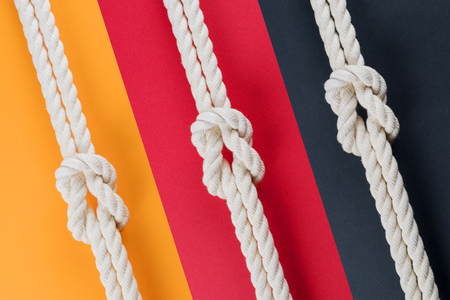 White ship ropes connected by reef knot. On colored background Reklamní fotografie
