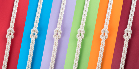White ship ropes connected by reef knot on colored strips background. Abstract colorful composition