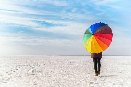 Woman with rainbow colored umbrella walking on frozen sea. Bright colored winter landscape 写真素材