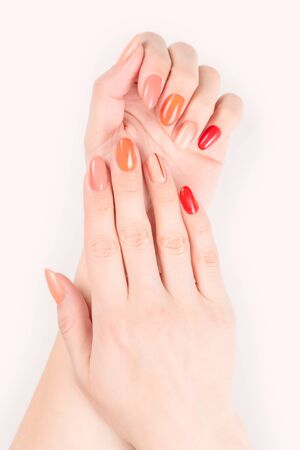 Perfect woman hands with red and pink colored nail polish. Isolated on pastel colored background, clipping path included