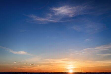 Bright colored winter sunset. Yellow clouds on the horizon and blue sky Stock Photo