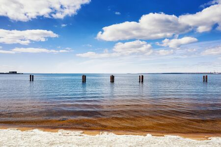 Bright colored sea landscape at sunny day. Clouds, coastal line and old pillars in the sea Stock Photo