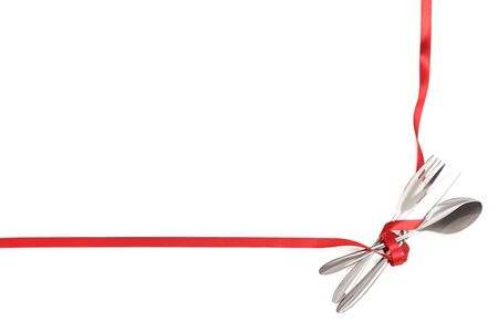 Fork, spoon and knife tied with a red ribbon. Isolated on white, clipping path included. Food, restaurant and table setting theme template with copy space Stock Photo