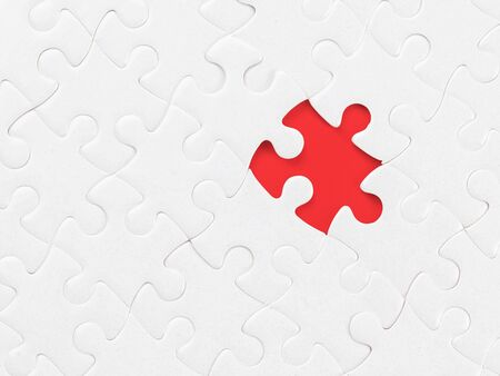 White blank jigsaw puzzle without one piece on red. Clipping path on the missing piece. Missing part, organization and solution theme Reklamní fotografie