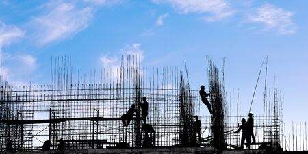 Workers on the building silhouettes on against blue sky. Construction industry and building under construction theme Stock Photo
