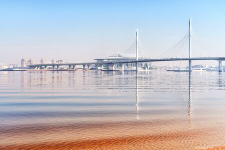Idyllic seascape in Saint Petersburg, Russia. Elevated highway road, bridge, distant stadium and their reflections into calm water Stock Photo