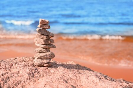 Stack of stones at sea coast at bright sunny day. Defocused blue water and sandy beach at background