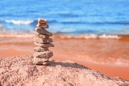 Steinstapel an der Meeresküste am sonnigen Tag. Unscharf gestelltes blaues Wasser und Sandstrand im Hintergrund
