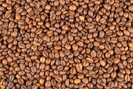 Raw coffee beans covered surface close up. Background and texture