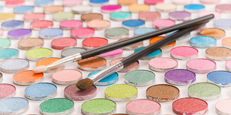 Two cosmetic brushes laying on large colored eye shadows bundle. Selective focus on the brushe
