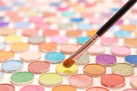Cosmetic brushes over large colored eye shadows bundle. Selective focus on the brushe