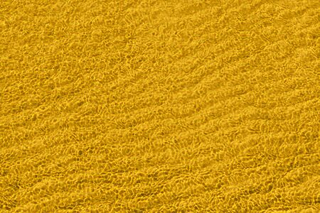 Yellow abstract waved surface close up. Texture and background