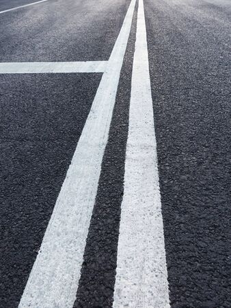 Asphalt road with white marking diminishing perspective