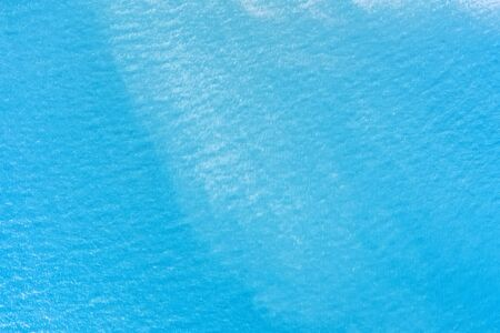 Calm sea surface aerial view. Aqua blue water with ripple texture and background