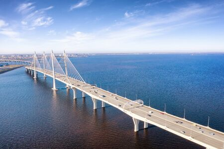 Traffic on the elevated highway over sea in Saint Petersburg, Russia aerial view. Landscape with bridge, cloudy sky and calm sea Stock Photo