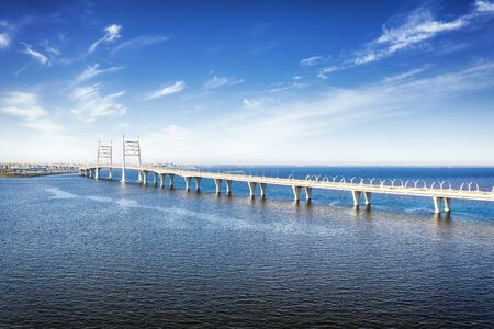 Elevated highway with bridge over sea in Saint Petersburg, Russia aerial view. HDR landscape with cloudy sky and calm sea