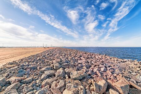 Wide angle sea coast industrial landscape with skyline, sand, sky stones and distant bridge in Saint Petersburg, Russia Stock Photo