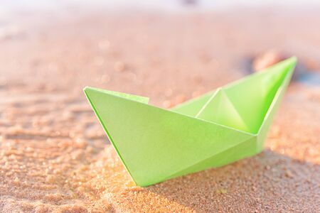 Green paper boat on sandy beach outdoors. Selective focus on the boat