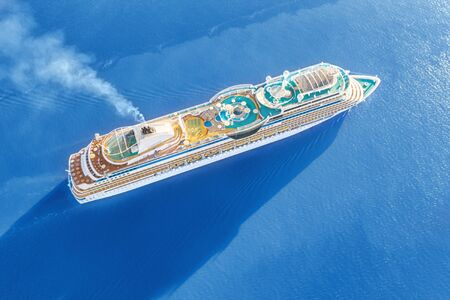 Luxury cruise ship sailing across the sea. Aerial view at sunny day
