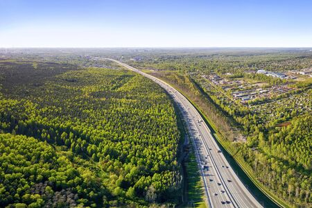 Traffic on the highway road  running to the horizon, forest and rural housing aerial panoramic landscape at summer day