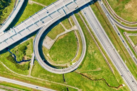 Big road junction fragment on green land aerial view, Highway intersection with traffic at sunny day