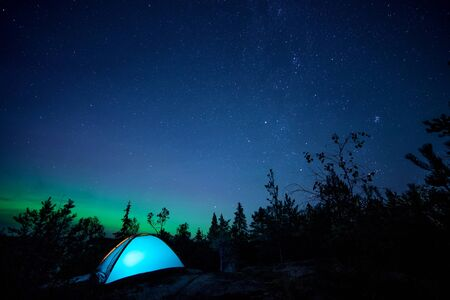 Night scene with illuminated camping tent, forest, starry sky and northern lights. Long exposure Reklamní fotografie