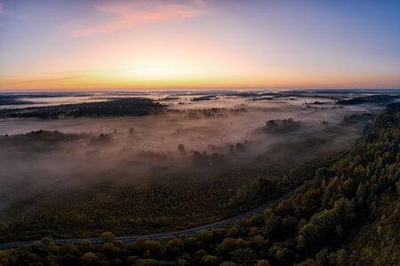 Fog over woodland at sunrise. Aerial panoramic landscape