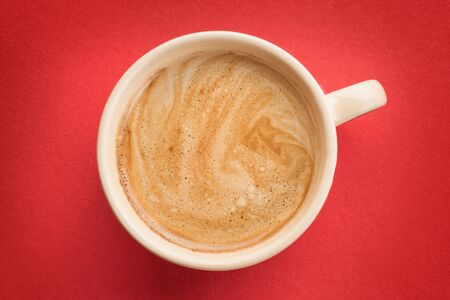Cream colored coffee cup with foam on red background top view