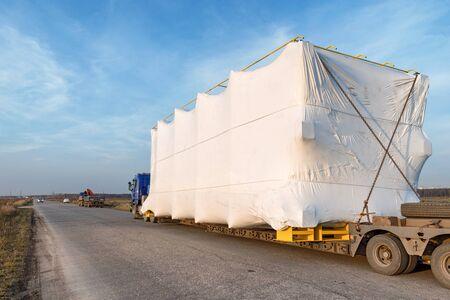 LKW mit großer übergroßer Ladung auf Landstraße. Industrielle Weitwinkellandschaft Standard-Bild